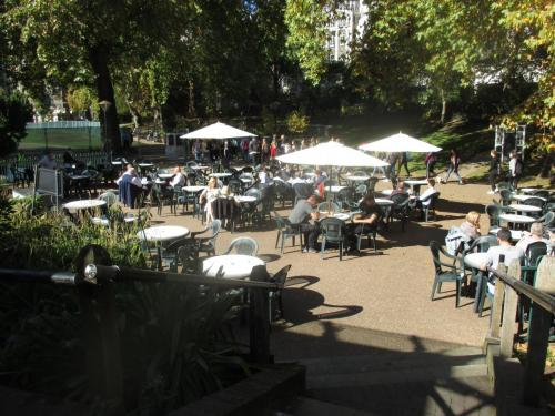 The action moves to London, making contact at an open air cafe under the sun umbrellas in Embankment Gardens